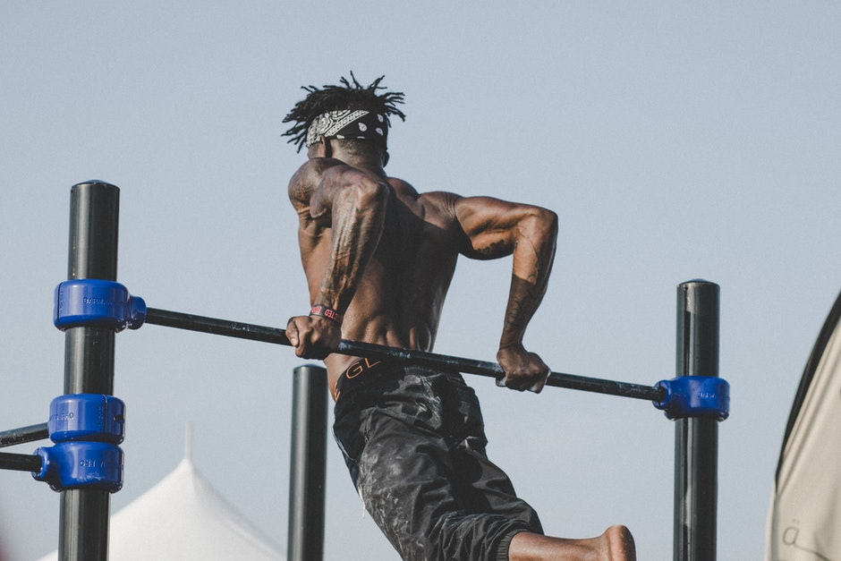 Man pulling himself up on a pullup bar - Home Gym Equipment