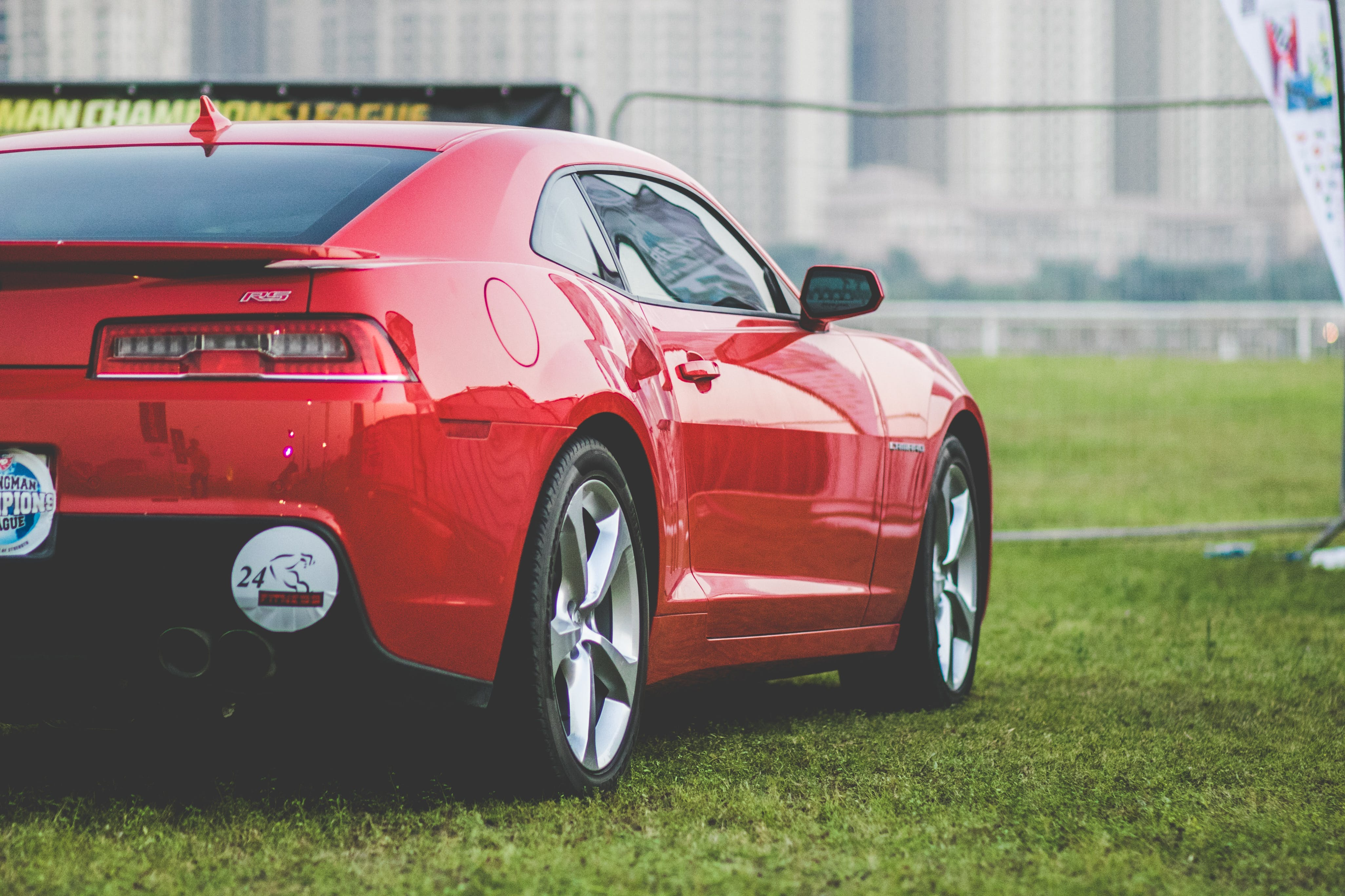 Red Coupe Parked on Green Grasses