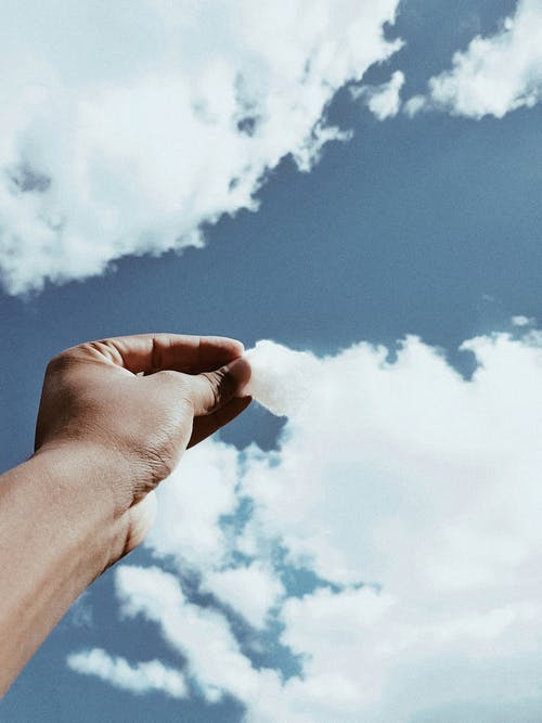 Person's Hand Across White Clouds