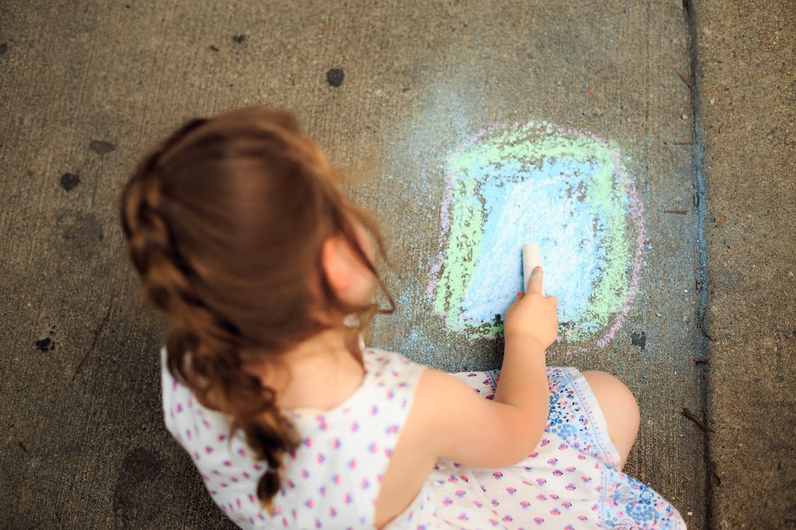 Little Girl Drawing on Pavement with Colored Chalk
