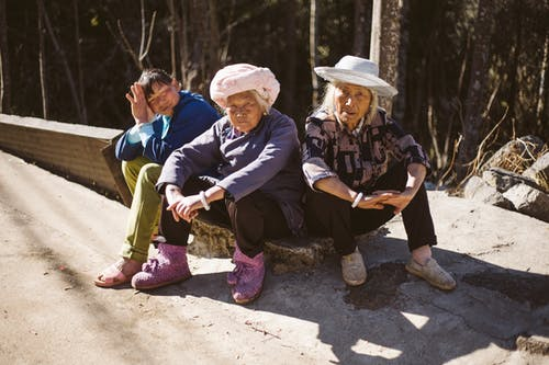 Three People Sitting Beside Pavement