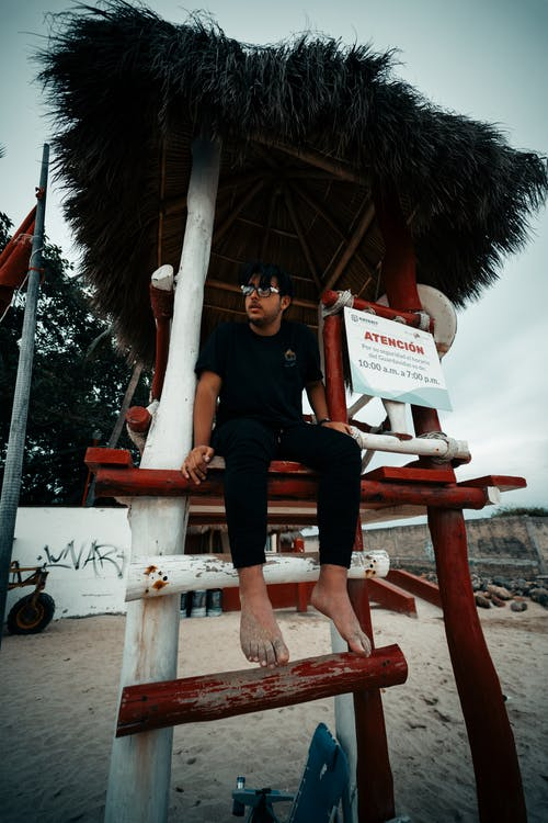 Photo of Barefoot Man in Black T-shirt and Pants Sitting in Lifeguard Tower