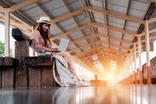 Low Angle Photo of Smiling Woman Using A Laptop Sitting on Wooden Bench at Train Station Platform