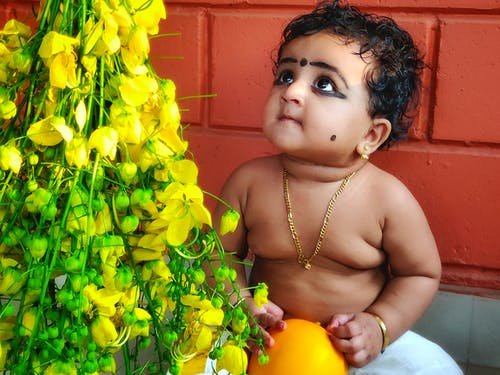 Free stock photo of Happy vishu with yellow flower and kid