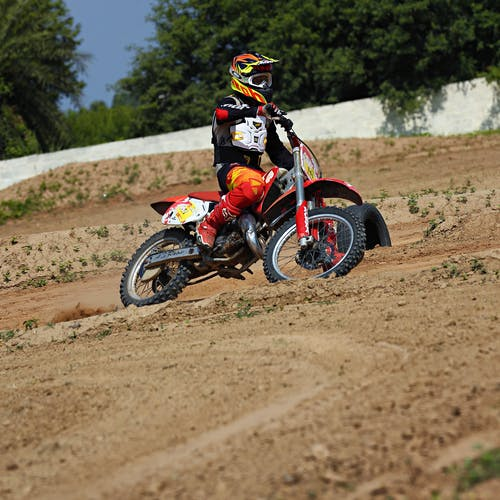 Person Riding Red Dirt Bike