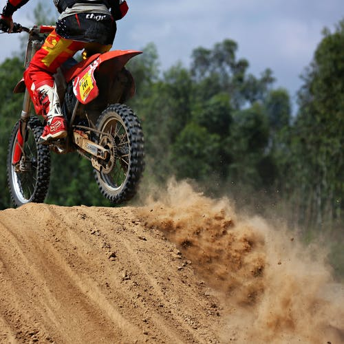 Man riding red dirt bike on track