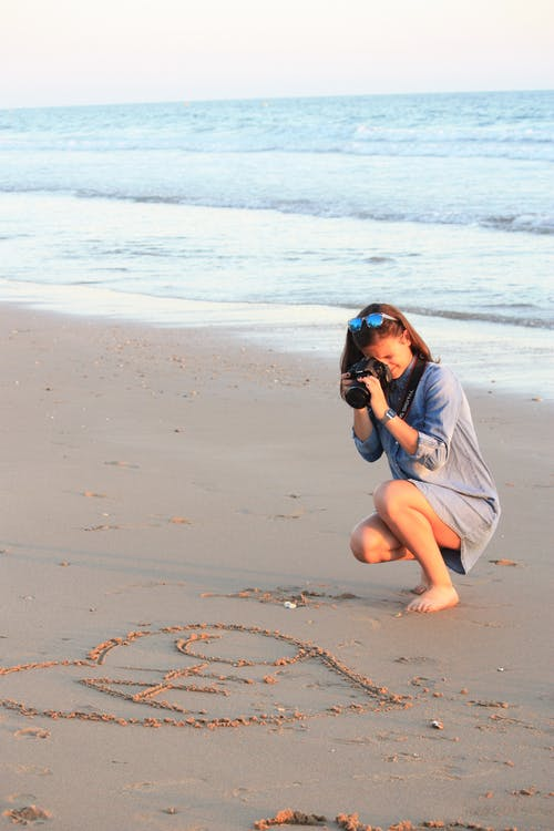 Photo of Woman Taking Picture of Heart Shape on Sand