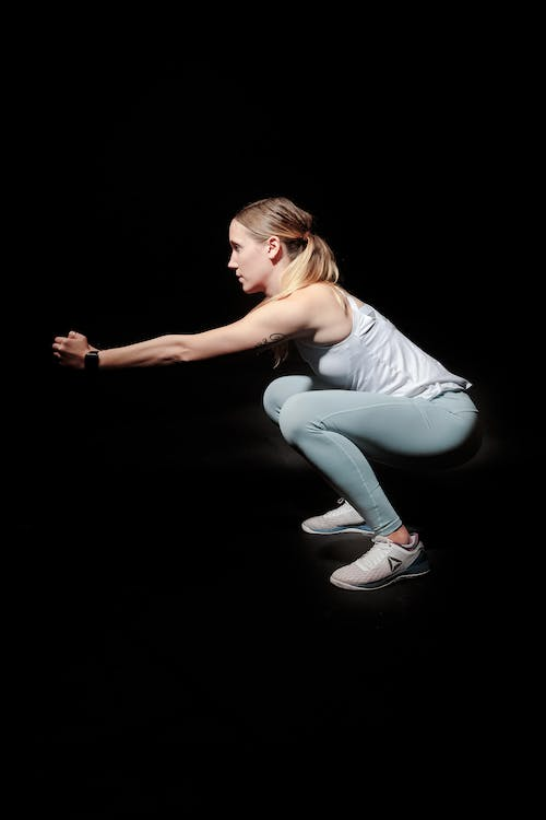 Side View Photo of Woman Doing Squats Against Black Background