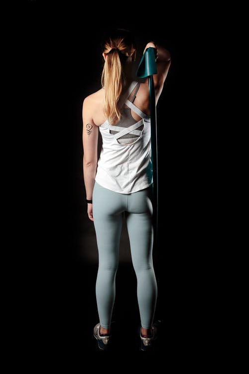 Back View Photo of Woman Pulling on Resistance Band With Right Arm Against Black Background