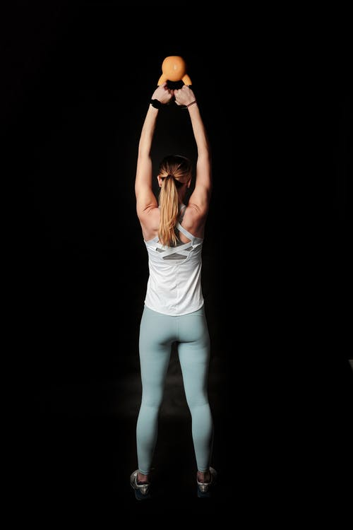 Back View Photo of Woman Carrying Kettlebell Against Black Background