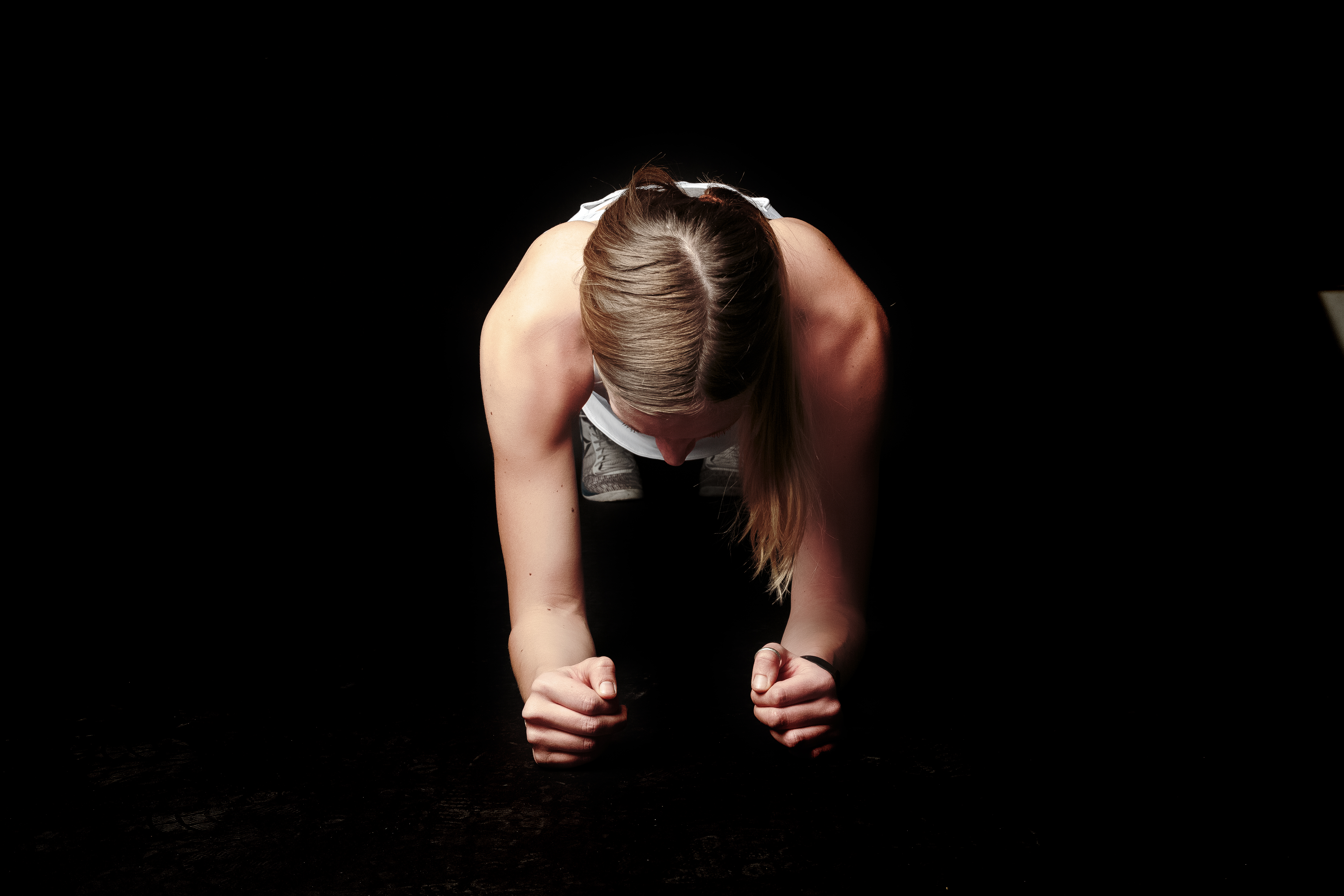 Photo of Woman Doing Plank against Black Background