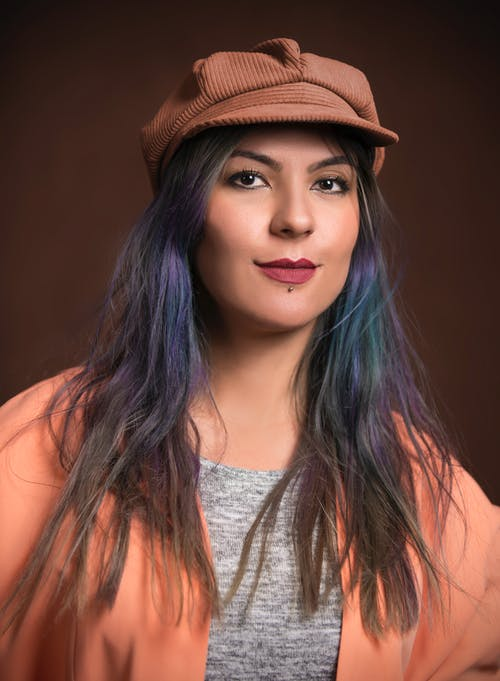 Portrait Photo of Woman in Brown Cap and Peach Cardigan Posing