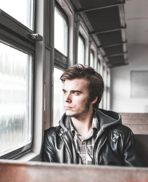 Photo of Man Sitting in Train Looking Outside Window
