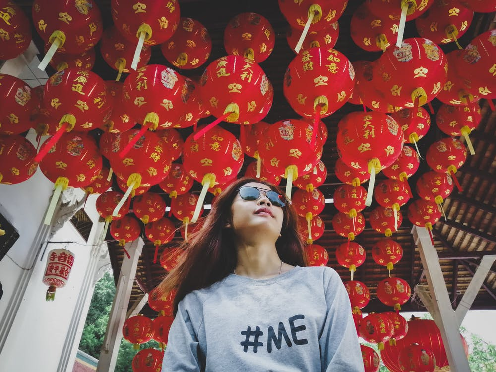 Low Angle Photo of Woman in Sunglasses Under Red Chinese Lantern