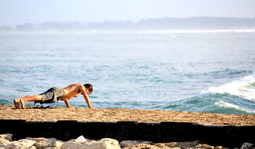 Man Doing Push Up on the Seashore