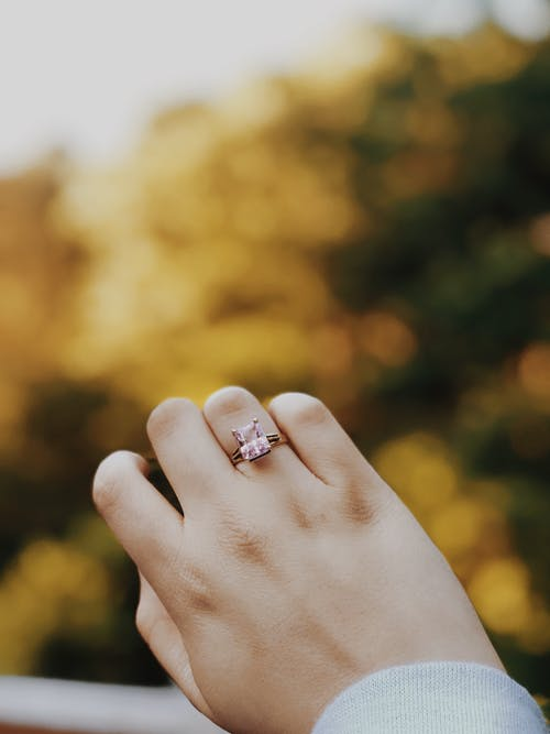 Person Wearing Silver-colored Ring With Pink Stone