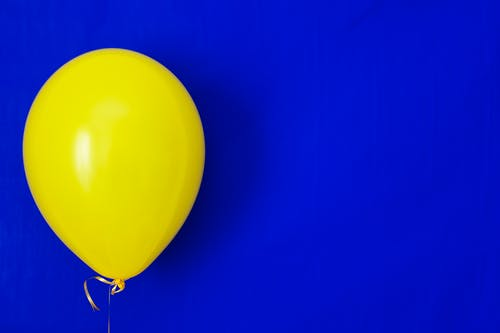 Yellow Balloon on Blue Background