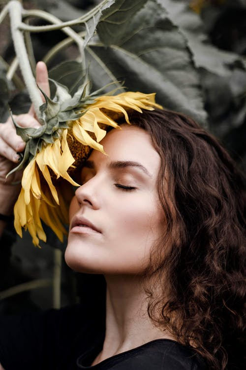 Side View Portrait Photo of Woman With Her Eyes Closed Posing With Yellow Sunflower Against Face