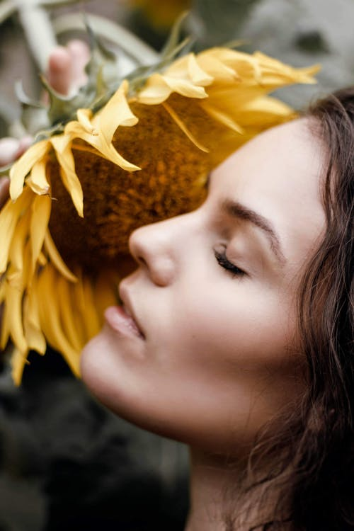Close-Up Photo of Woman Near Sunflower
