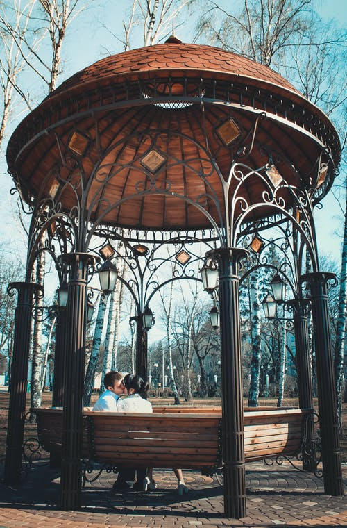 Couple About to Kiss Sitting on Metal Gazebo