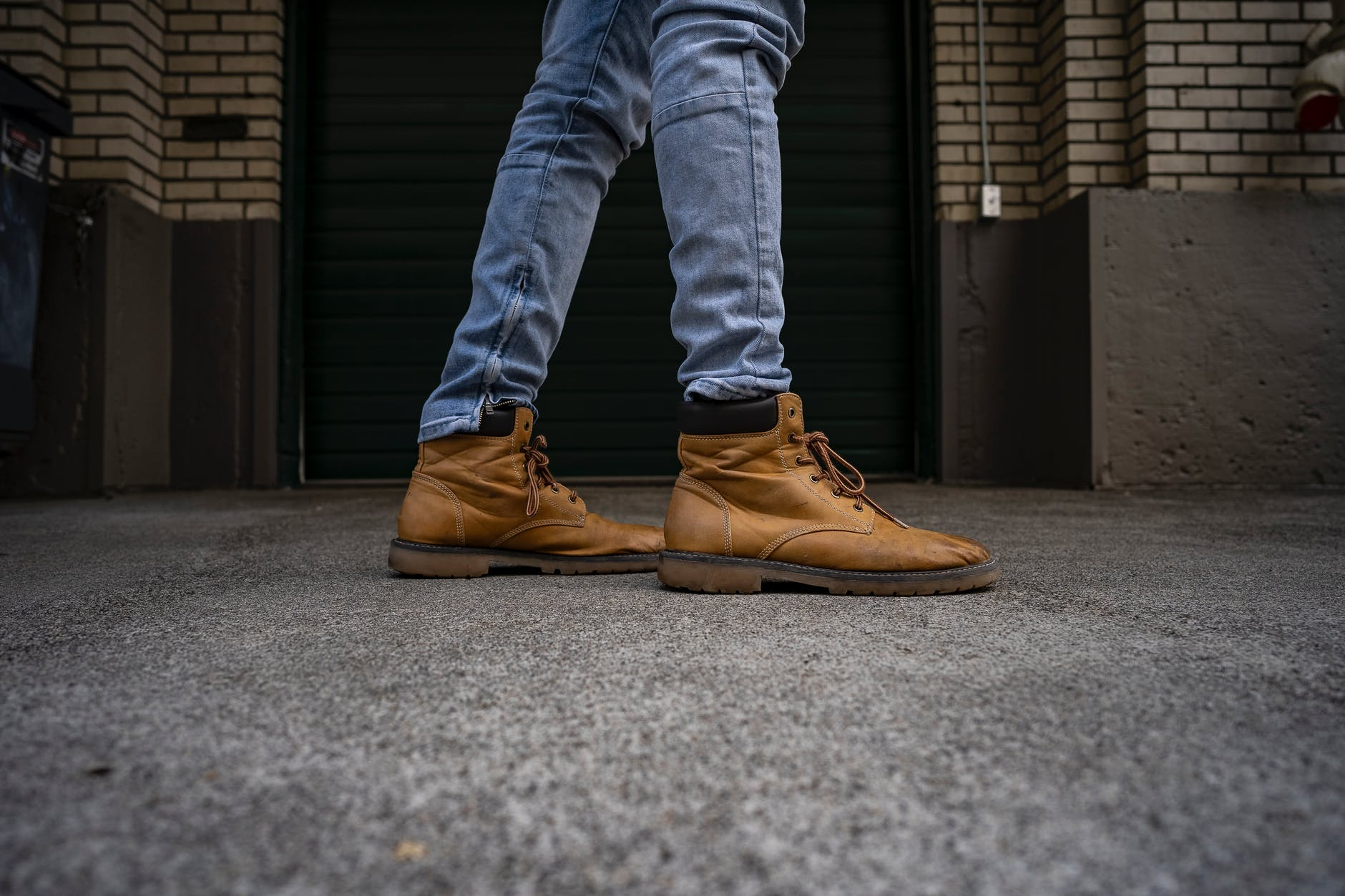 A person is wearing a blue jeans and a brown work boots