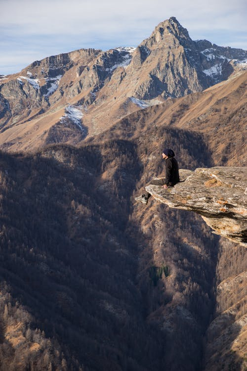 Aerial Photography Man Sitting on Mountain Cliff