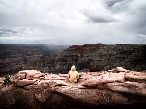 Person Sitting On Brown Rock Formation