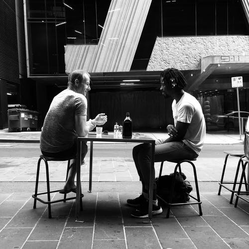 Photo of Two Men Talking While Sitting on Chair