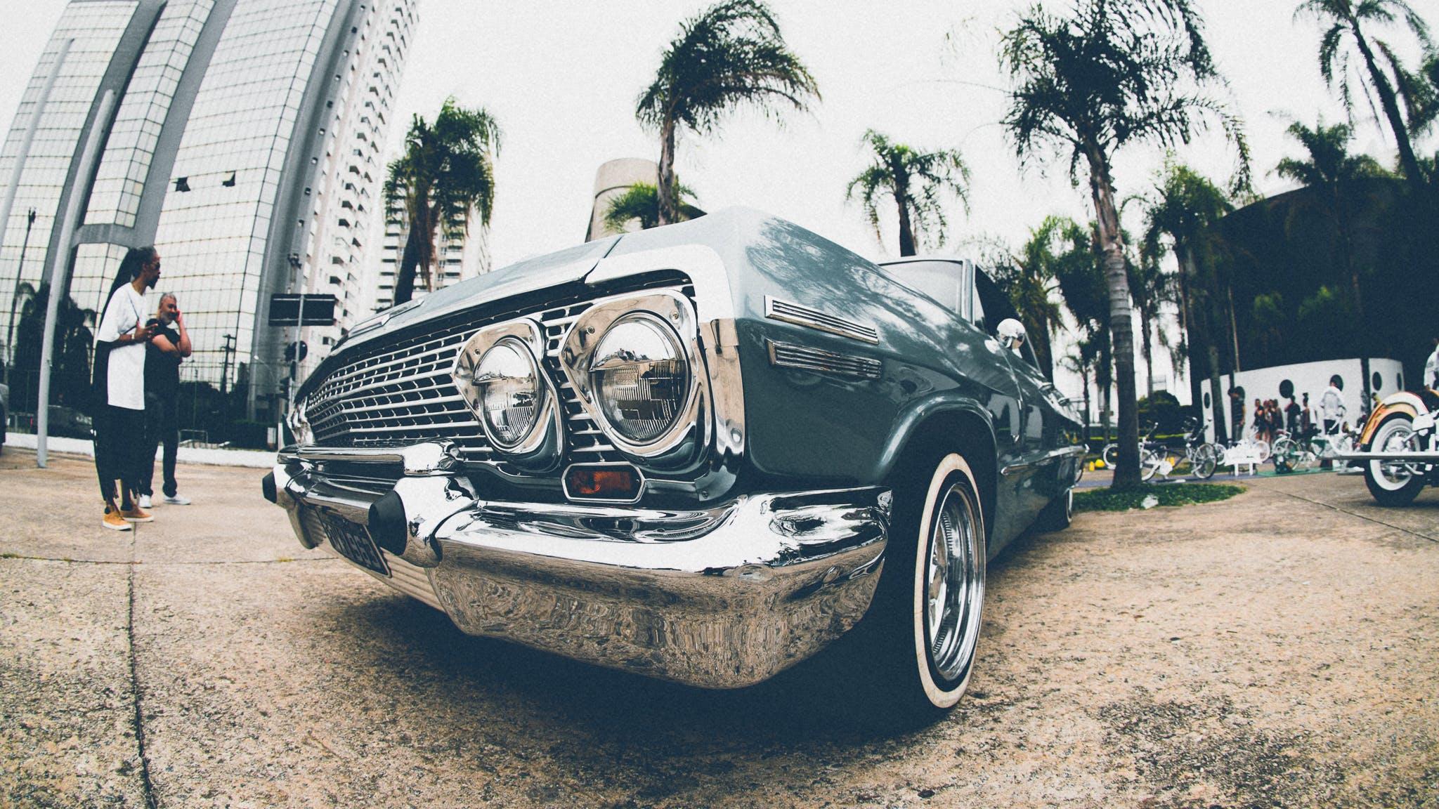 Classic Blue Chevrolet Impala Parked Beside Man