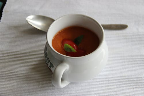 White Ceramic Mug with Soup Beside Spoon