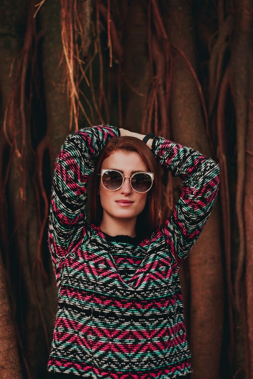 Photo of Woman in Sunglasses Posing with Her Hands Over Her Head While Standing In Front Tree
