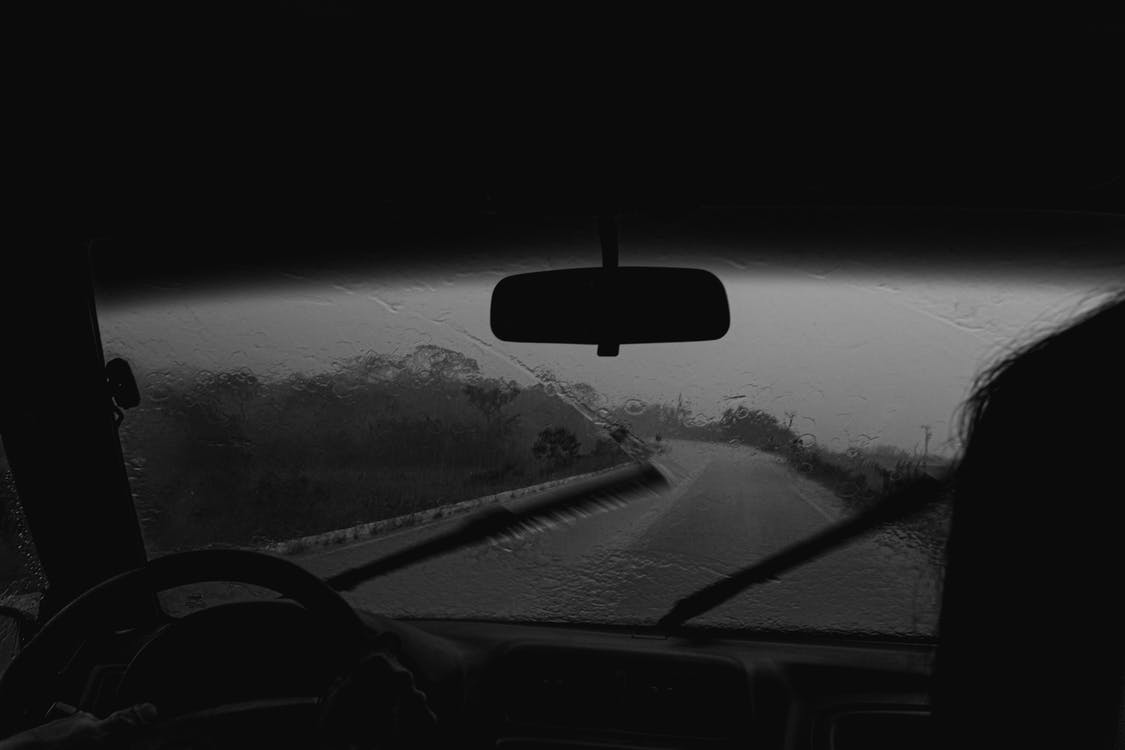Photo of Person Driving a Car While Raining