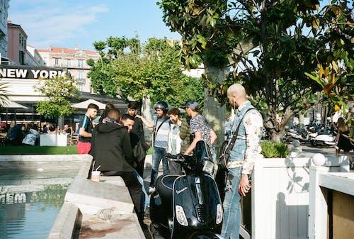 People Standing Beside Black Motor Scooter