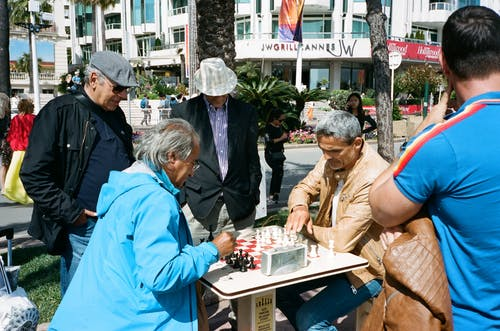 People Watching Two Men Playing Chess