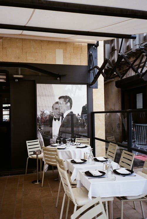 Two Men in Black Suit Jackets Poster In A Restaurant