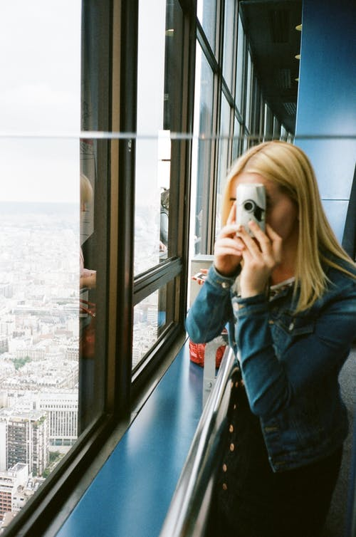 Photo of Woman Taking Picture of Glass Windows