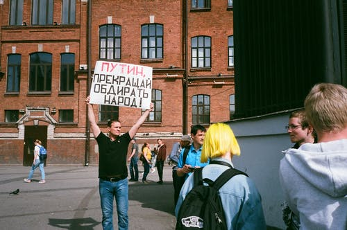 Man Standing Outdoor While Holding Signage