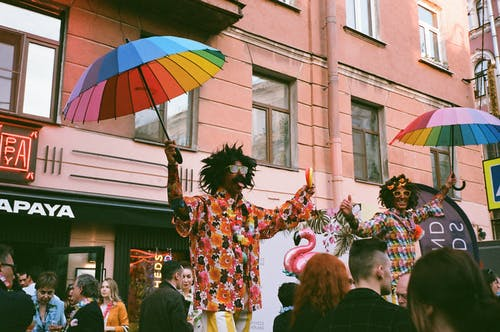 Two Men Performs on Stage While Holding Rainbow Colored Umbrellas