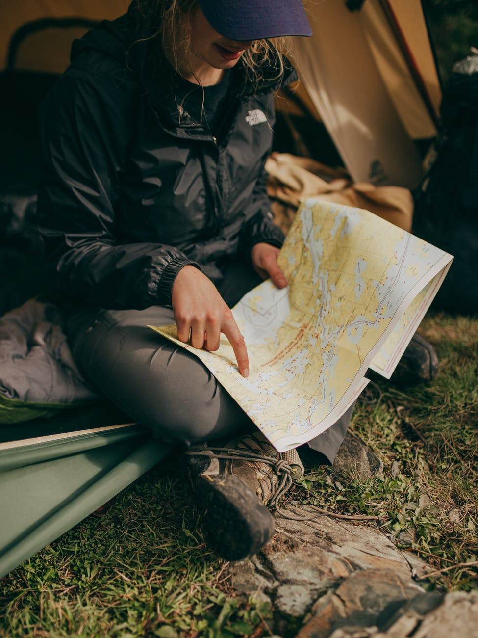 girl woman in thent camping pointing on map