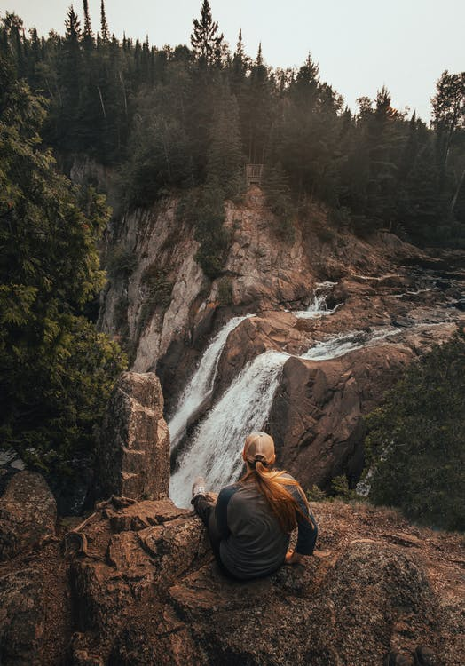 Woman Sitting on Rock While Staring on Waterfall