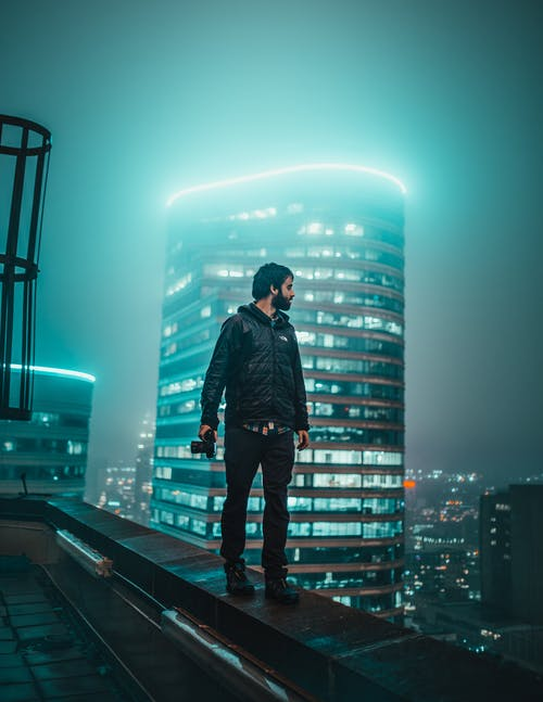 Photo of Man Holding Dslr Camera Walking on Edge of Building Overlooking at Night