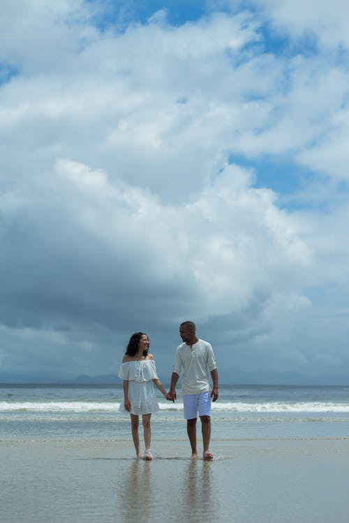 A Man and a Woman Walking on a Beach Holding Hands