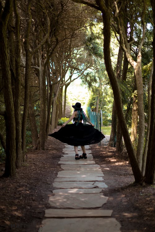 Selective-focus Photography of Woman Walking on Pathway Between Trees