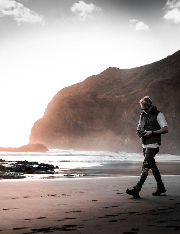 Man Walking Near Beach Line