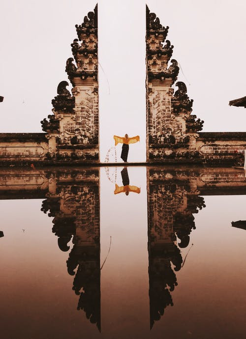 Woman Wearing Dress Standing Near Concrete Building With Reflection to Water