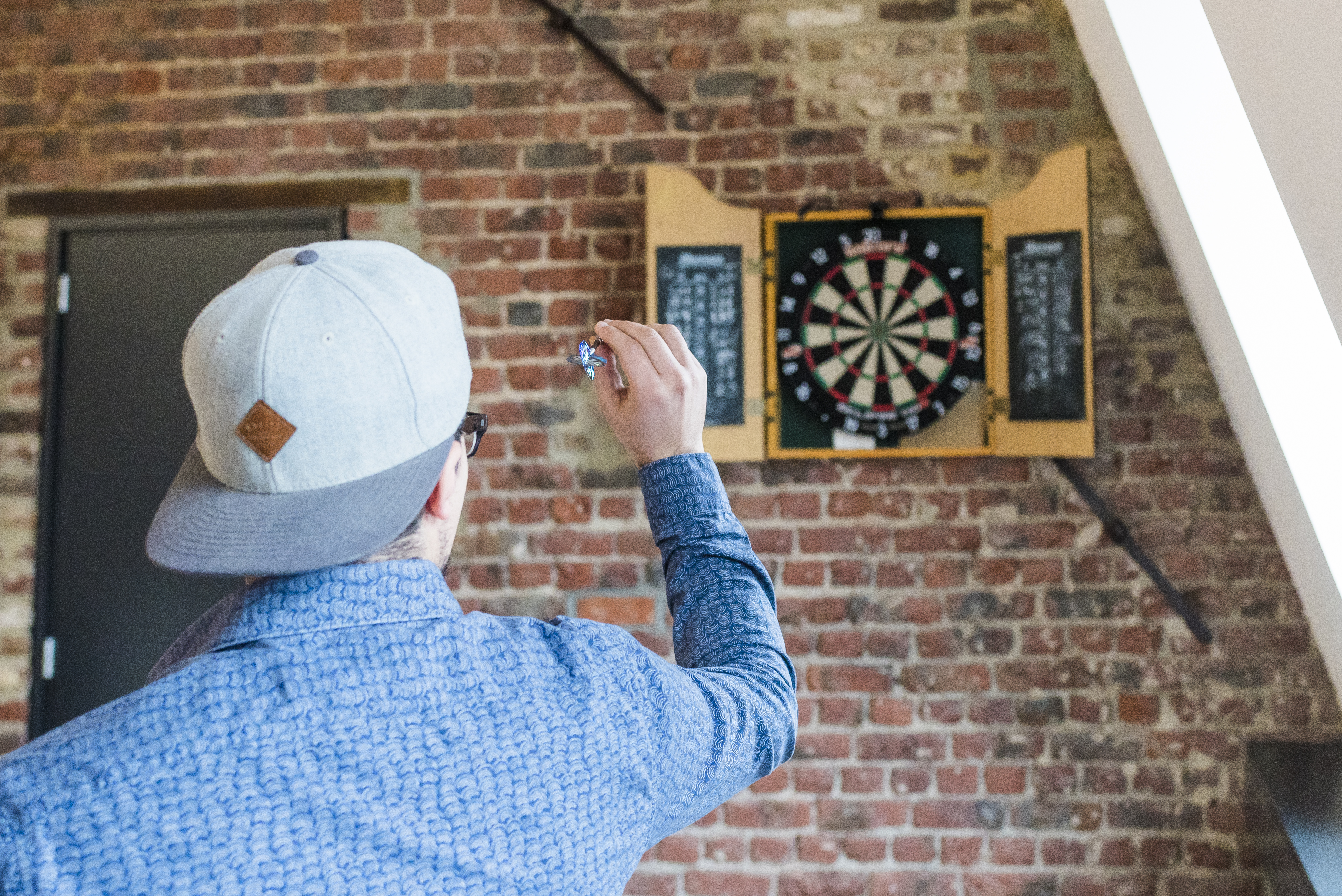 Back View Photo of Man in Blue Dress Shirt and Gray Hat Playing Darts