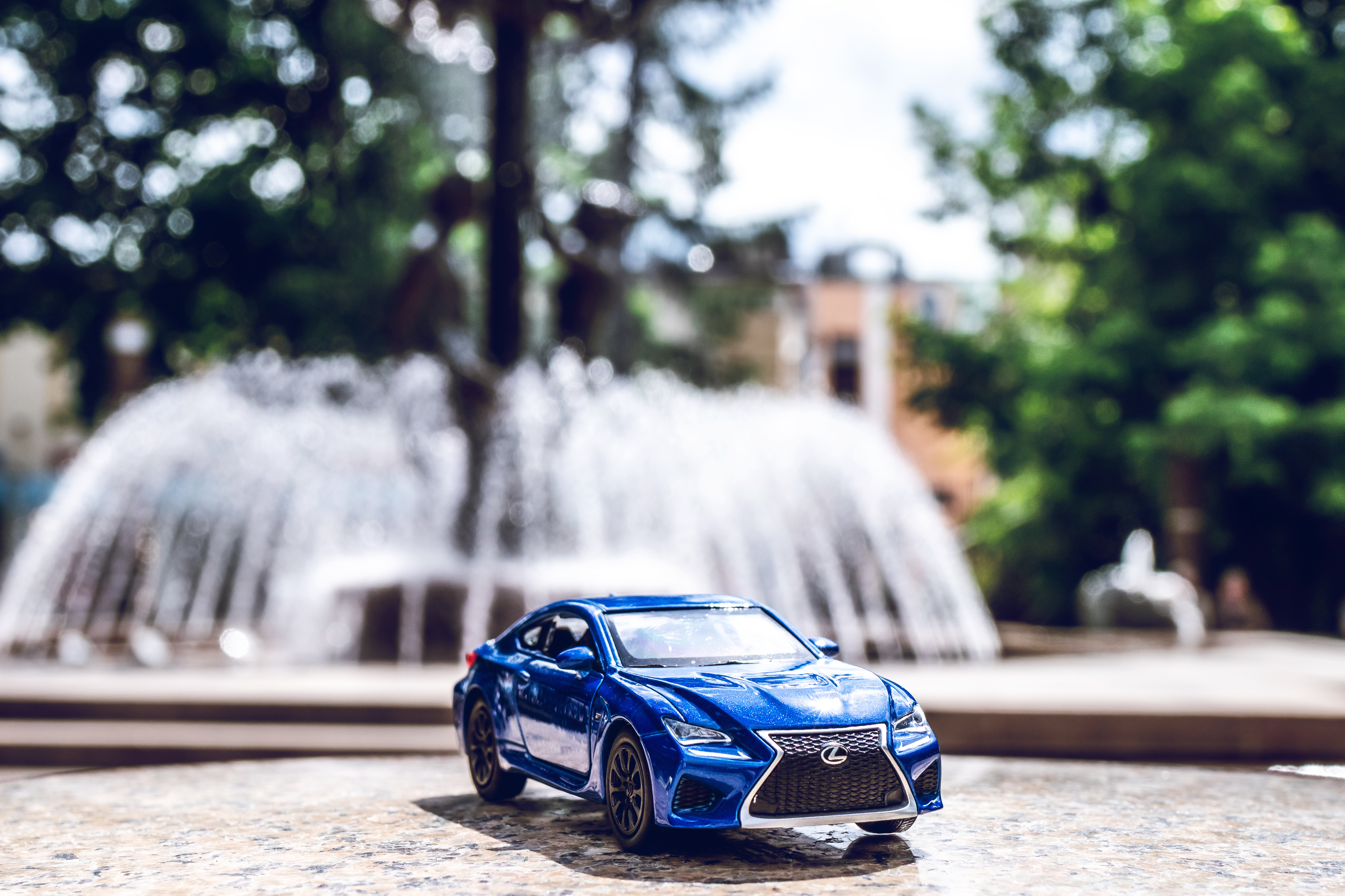 Blue Die-cast Toy Car Across Outdoor Fountain