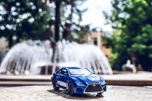 Blue Die-cast Toy Car Across Outdoor Fountain