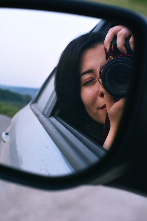 Woman Taking Picture On Vehicle Mirror