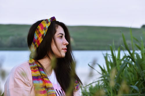 Side View Photo of Woman in Pink Top and Multi-colored Headscarf Sitting Next to Tall Grass With Body of Water in the Background